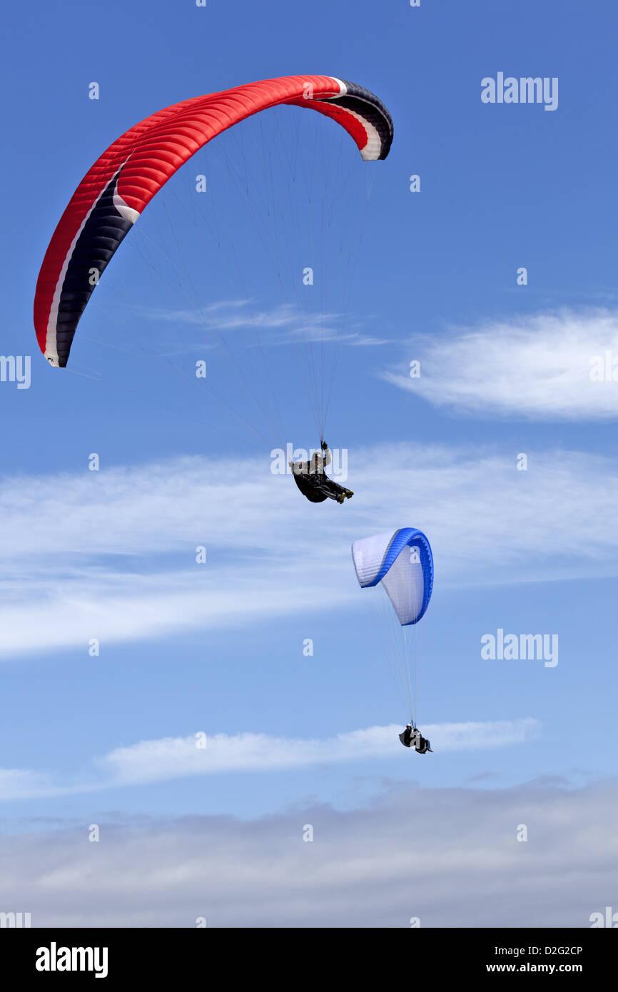 A single  Niviuk Artik 2 paraglider soaring with a BiGolden 2 tandem paraglider in the background - Stock Image