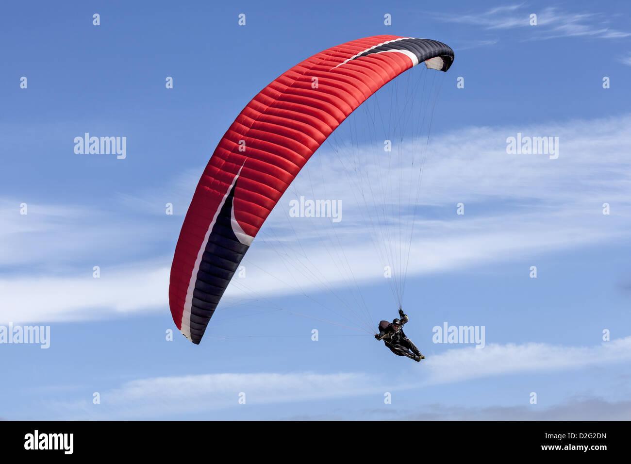 A single paraglider soaring with his Niviuk Artik 2 chute - Stock Image