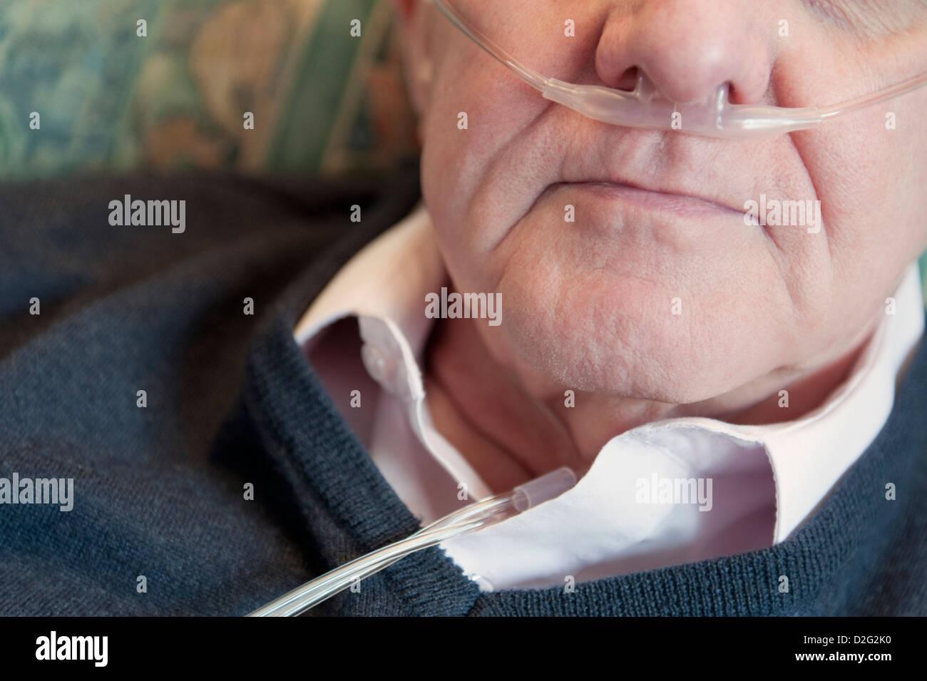 Portrait of an elderly man wearing oxygen nasal tube - Stock Image