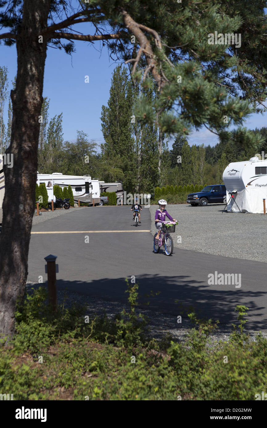 Kids riding bicylces around a RV park in Pedder Bay RV Resort and Marina near Metchosin Vancouver Island, BC, Canada - Stock Image