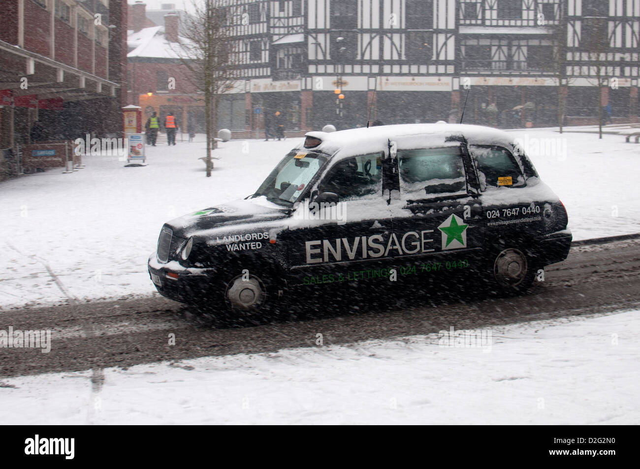 Taxi in snowy weather, Coventry city centre, UK - Stock Image