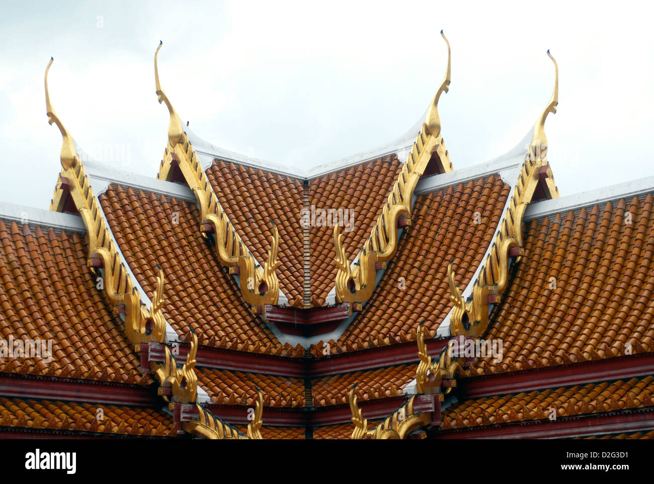 Roof top of a temple in bangkok with guilded bai raka naga fins and feathers of Garuda and the serpentine like lamyong - Stock Image
