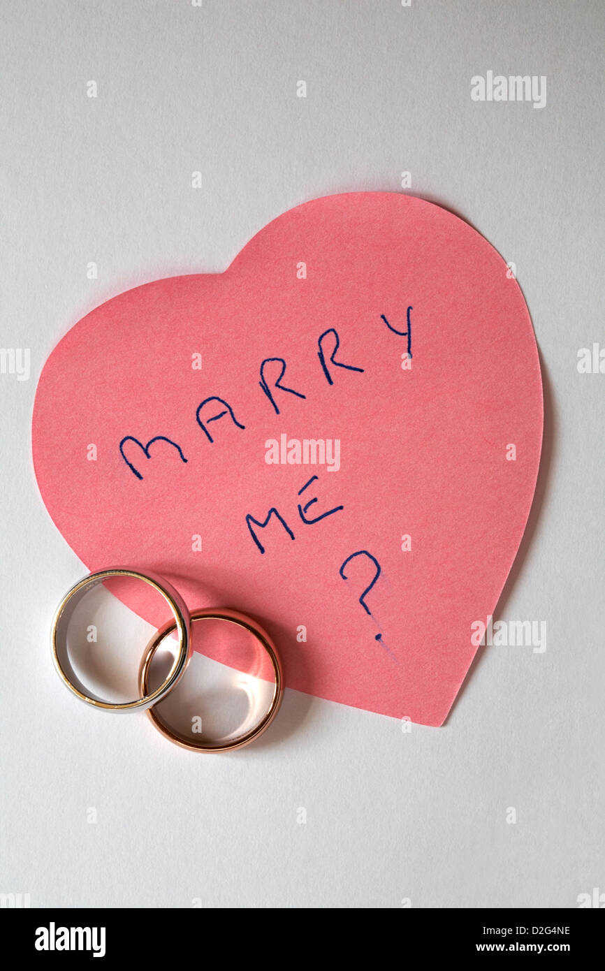 marry me? message written on pink heart shaped post it pad with two wedding rings - marriage proposal isolated on - Stock Image