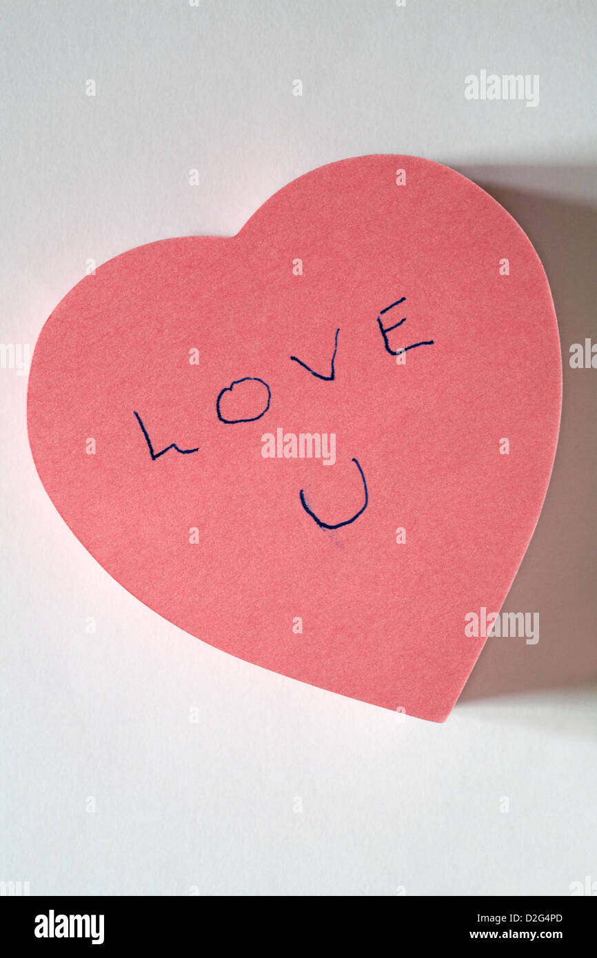 love u message written on pink heart shaped post it note pad isolated on white background - Stock Image