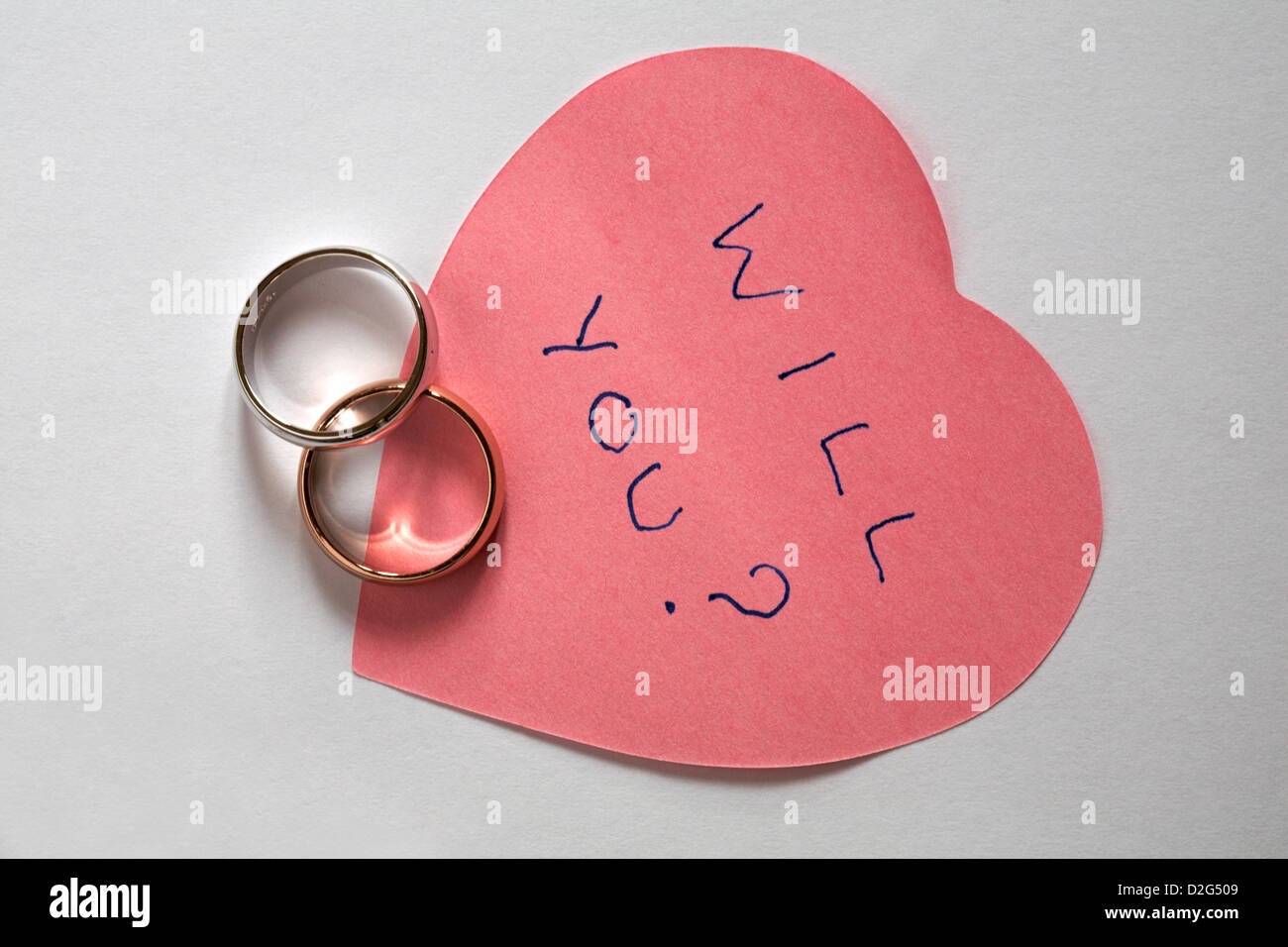 will you? message written on pink heart shaped post it pad with two ...