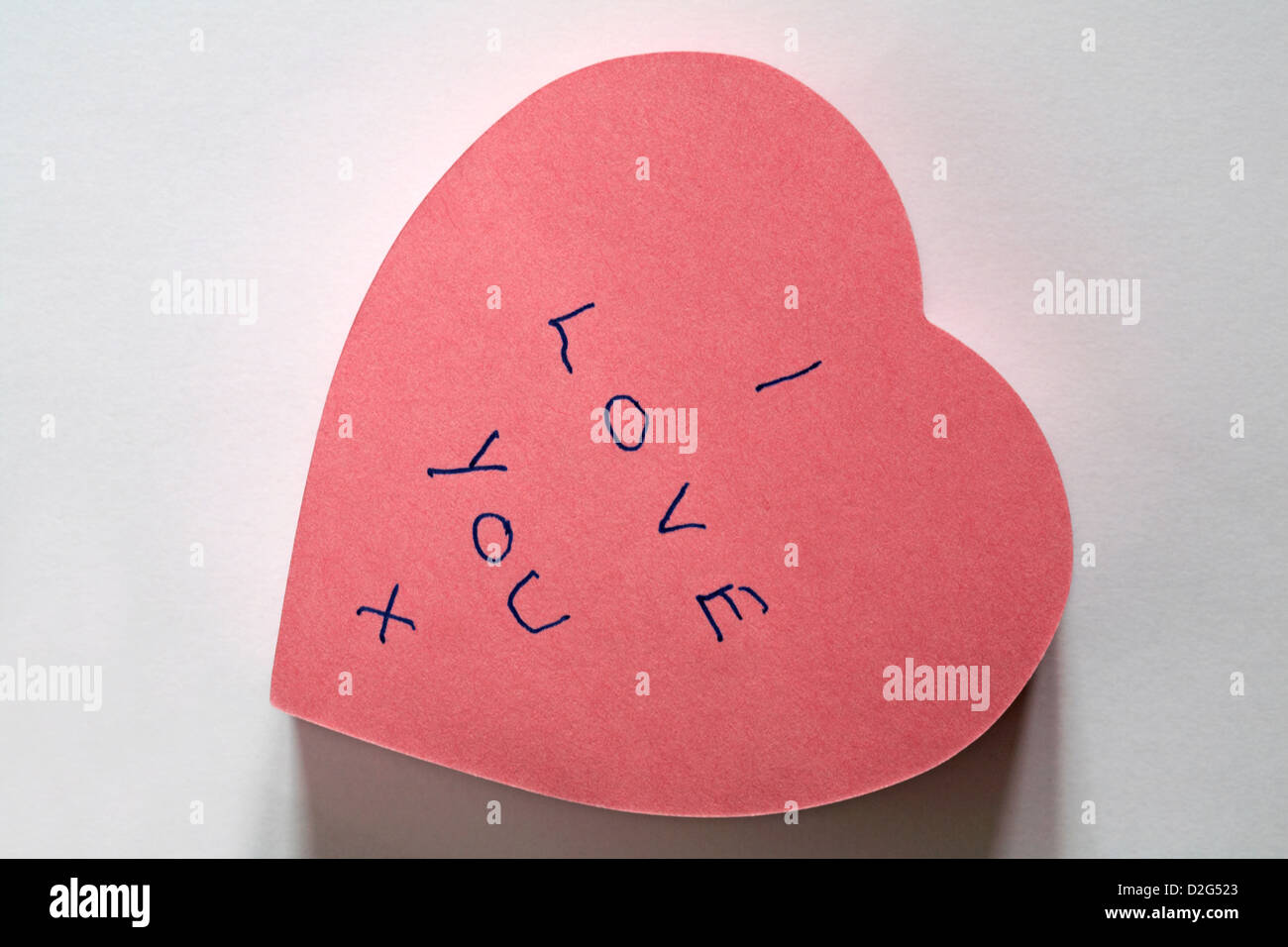 I Love you x message written on pink heart shaped post it note pad isolated on white background - Stock Image