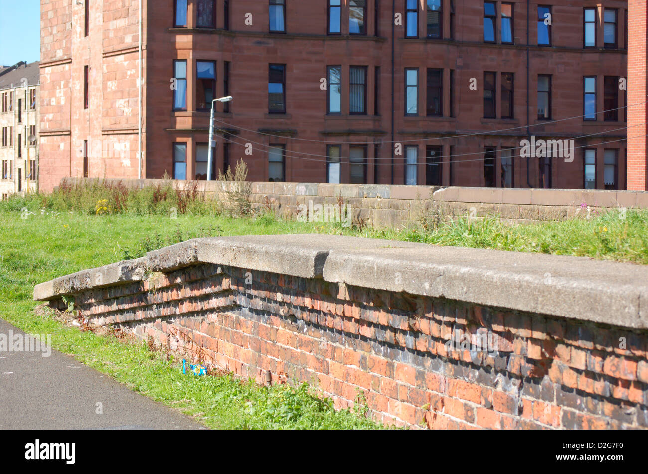 Tenement buildings next to abandoned railway line in Glasgow, Scotland - Stock Image