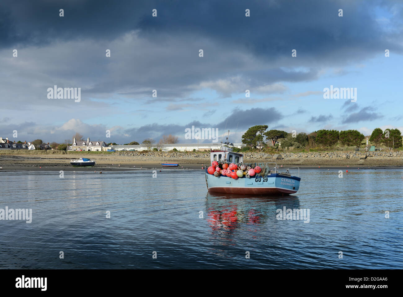 A fishing trawler at low water, Guernsey as storm clouds approach - Stock Image