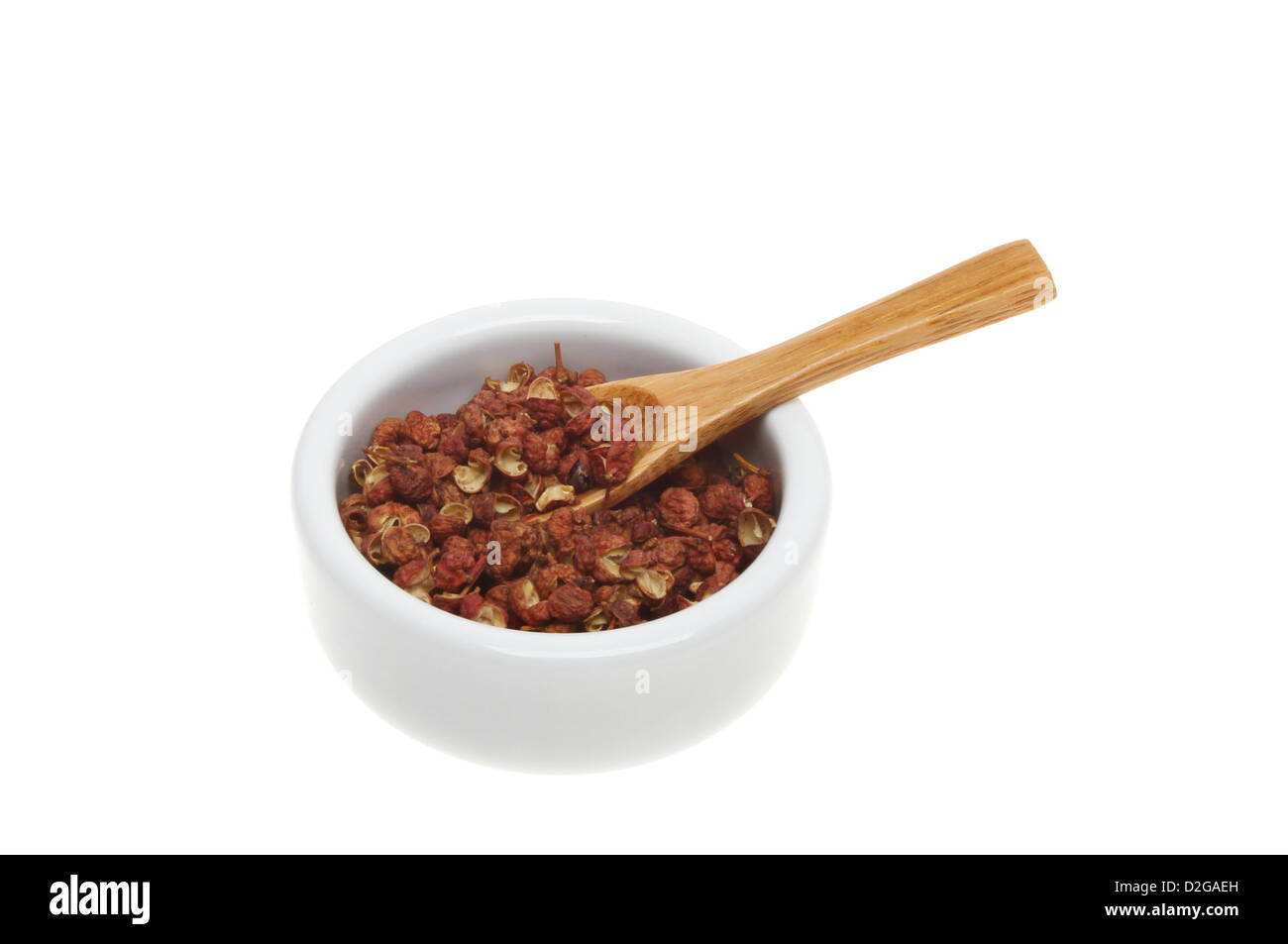 Szechuan pepper with a wooden spoon in a ramekin isolated against white Stock Photo