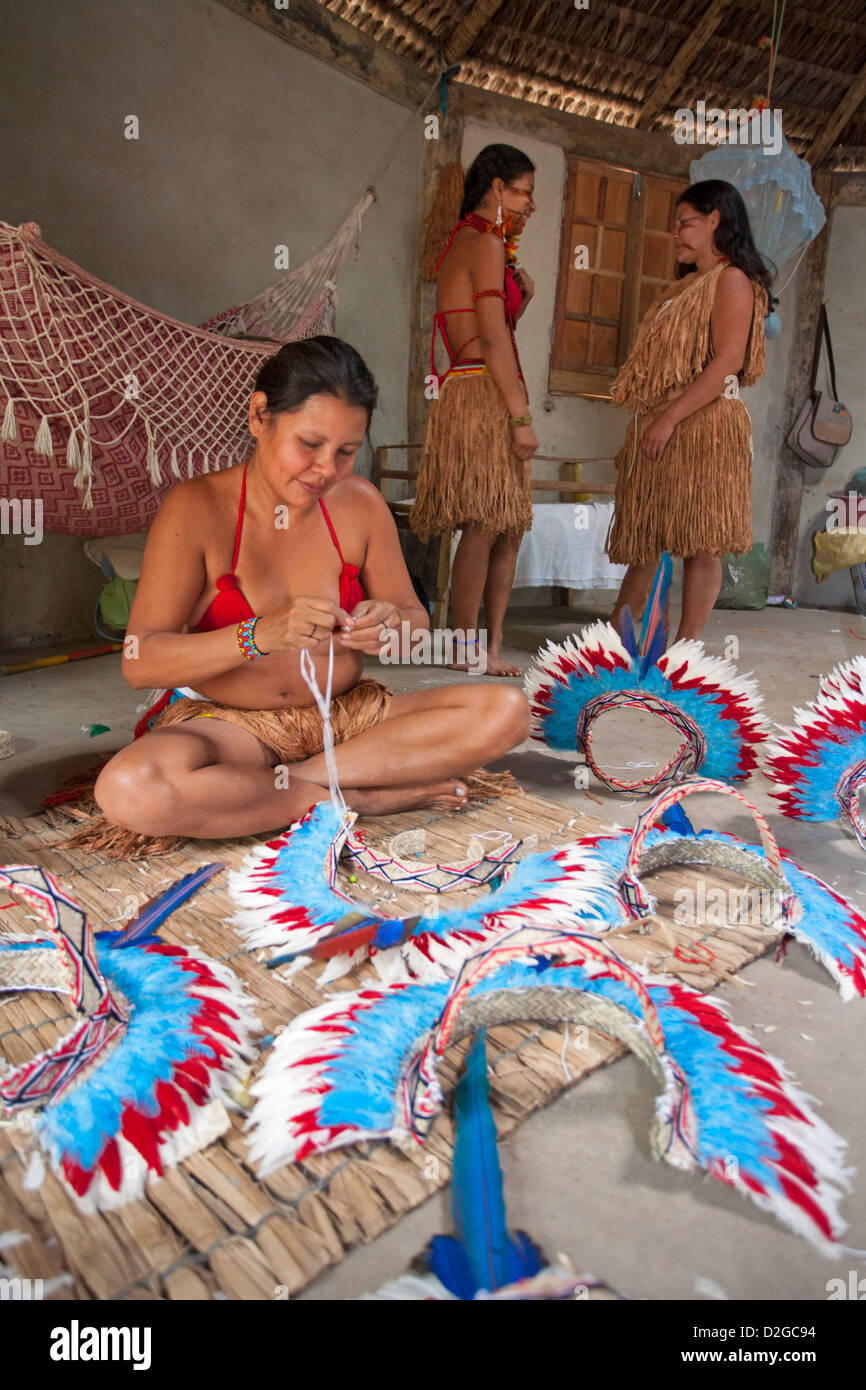 Pataxo indigenous women making feather head dresses - Stock Image