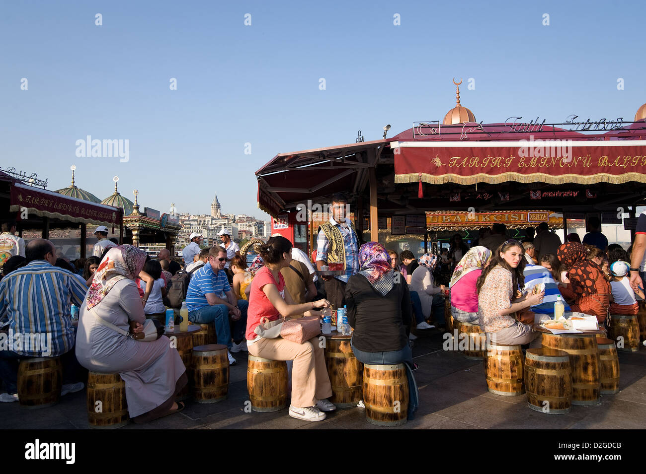 Tourists and Turks alike love to eat fishbread at the waterfront of the Golden Horn in Eminonu at the end of Galata - Stock Image