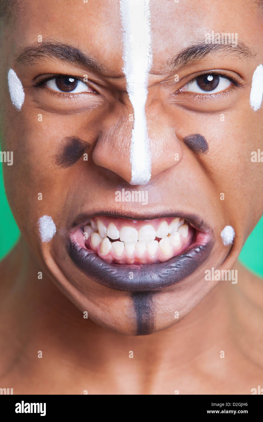 Detail shot of aggressive mixed race man with painted face clenching teeth - Stock Image