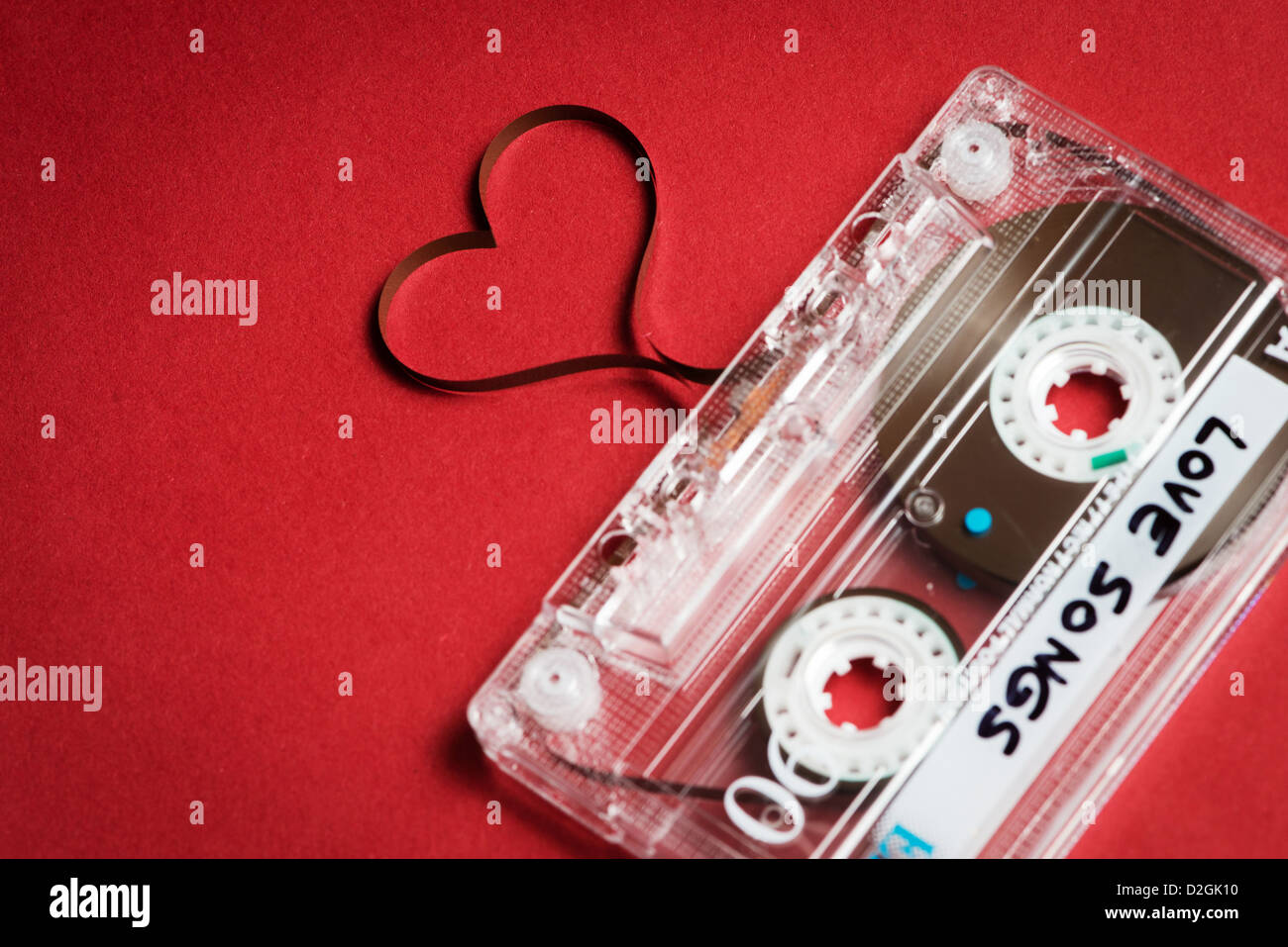 Valentine's day card template - audio cassette with magnetic tape in shape of heart on red background - Stock Image