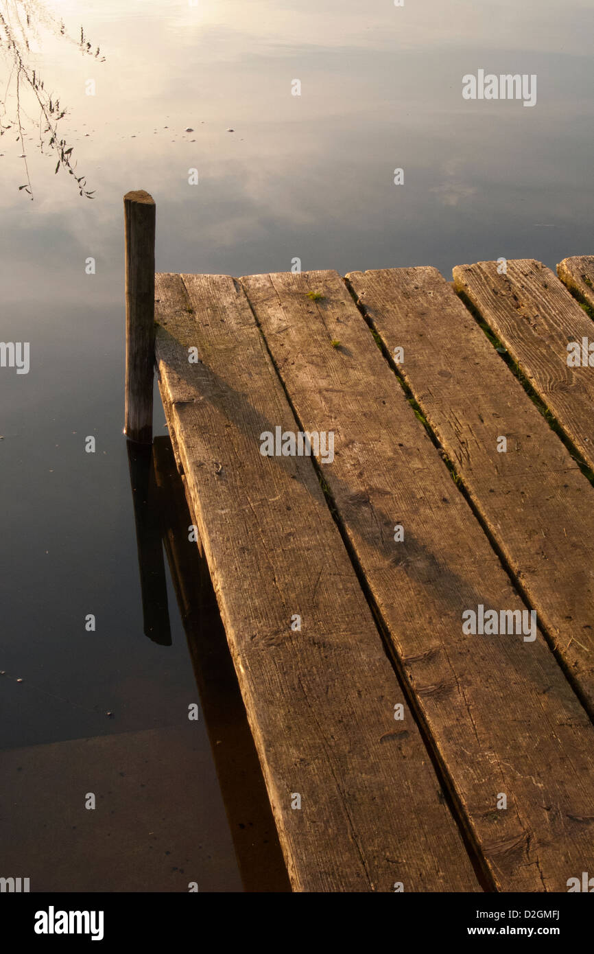 Wooden Jetty pier by lakeside in late afternoon light - Stock Image