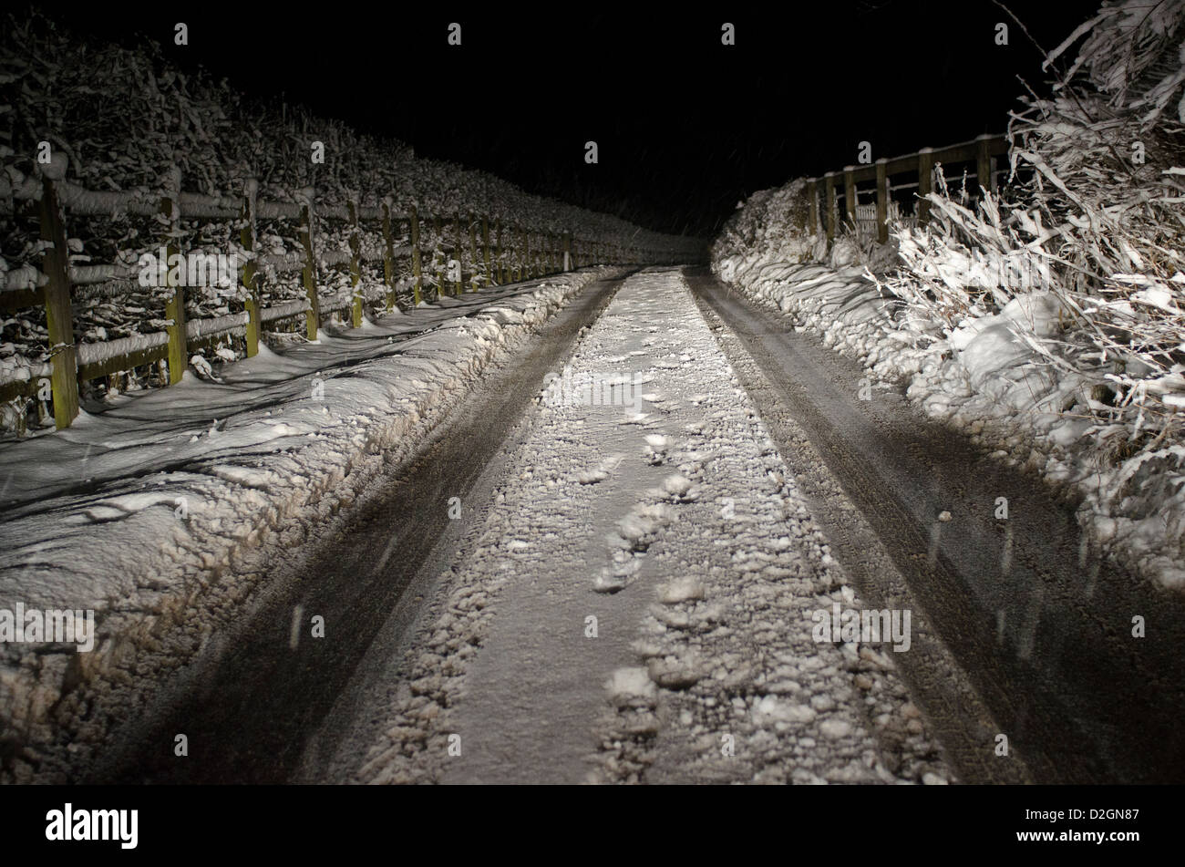 Narrow country road in snow at night - Stock Image