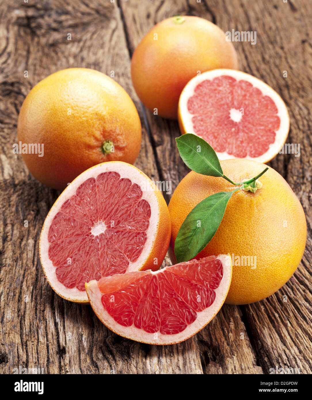 Grapefruit with slices on a wooden table. Stock Photo