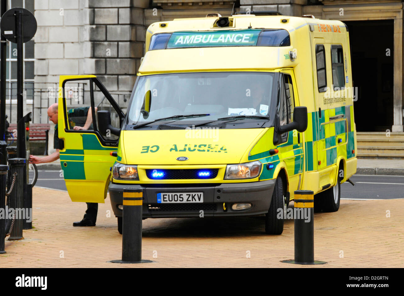 Ambulance driver on emergency call trying to push buttons to gain access to Chelmsford pedestrianised shopping high - Stock Image