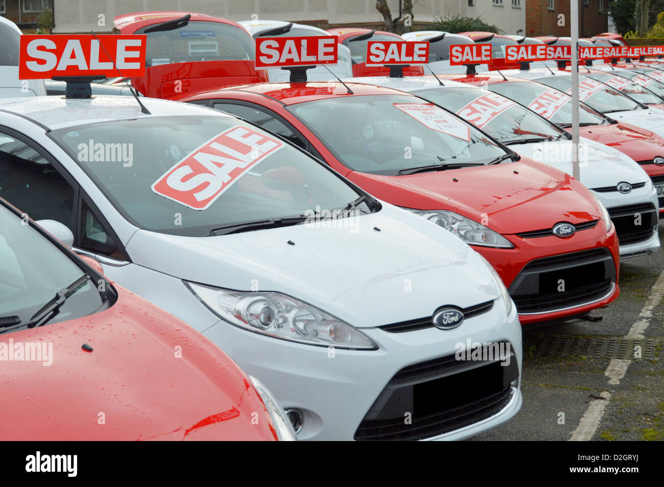 Sale of used Ford cars on car dealership forecourt outside showroom arranged alternate red and white obscured numberplates - Stock Image