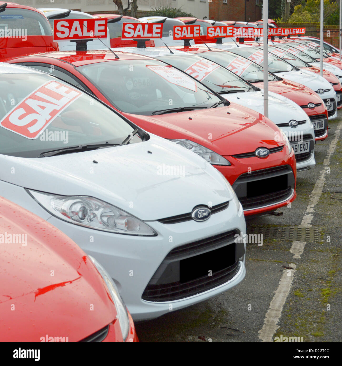 Ford cars for sale on main dealership forecourt outside showroom arranged alternate red and white obscured numberplates - Stock Image