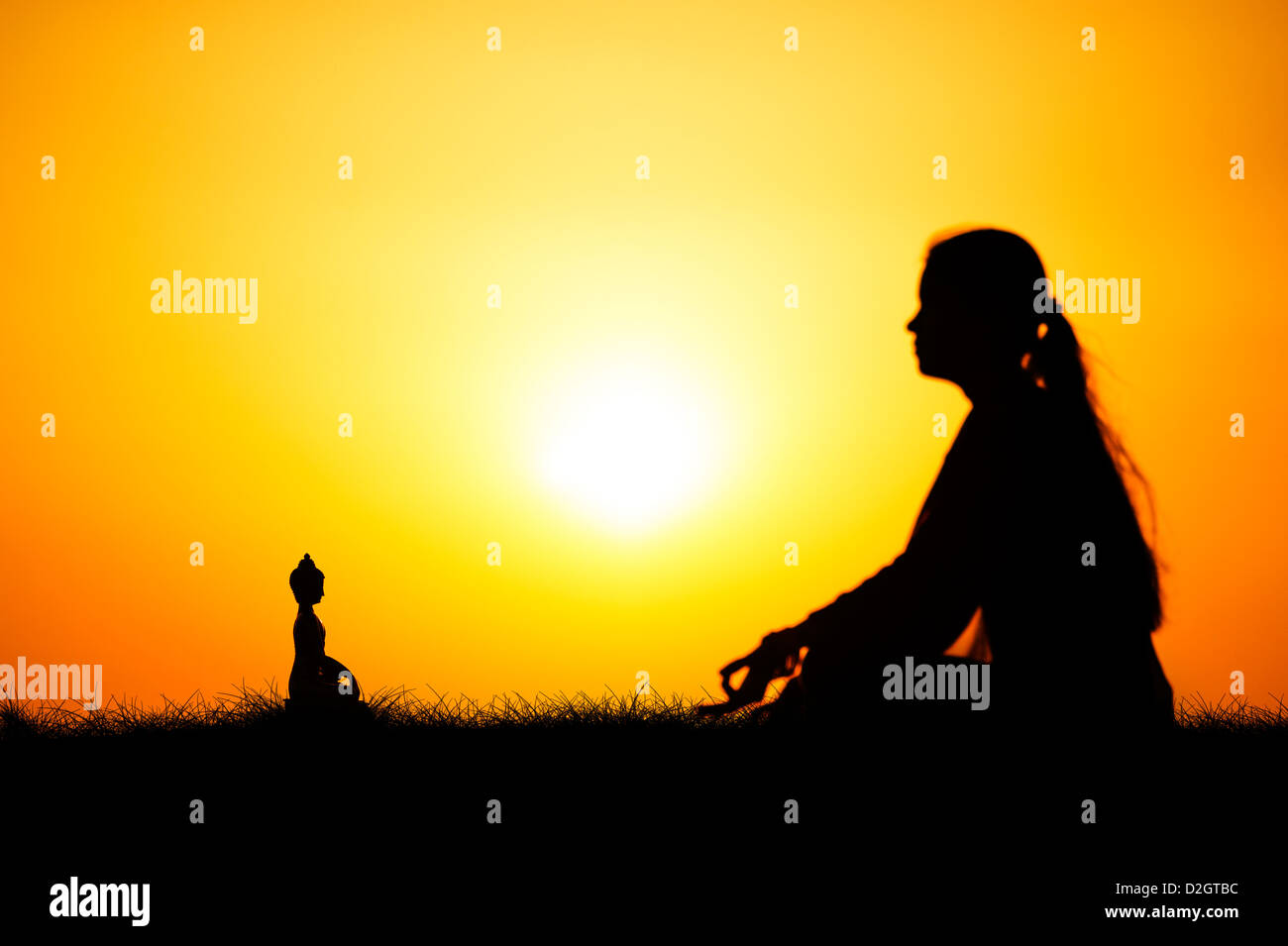 Sunset silhouette of an Indian girl meditating in front of Buddha statue. Andhra Pradesh, India - Stock Image