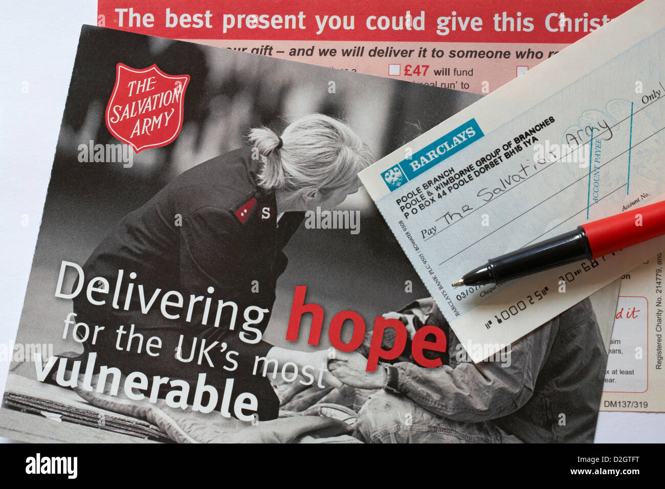 Writing cheque to The Salvation Army with info from charity Delivering hope for the UKs most vulnerable the best - Stock Image