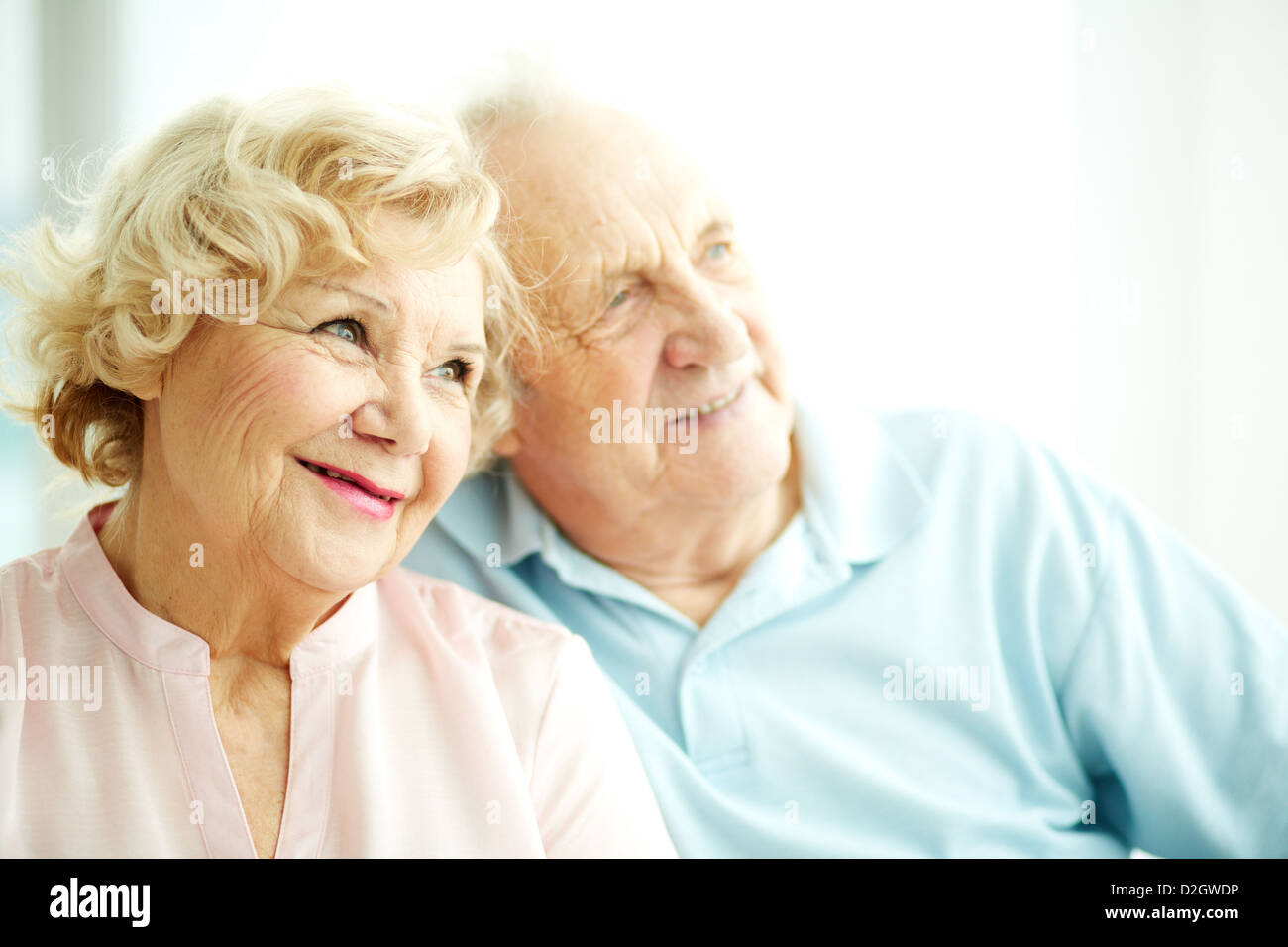 Close-up portrait of a charming elderly woman with her husband on background - Stock Image