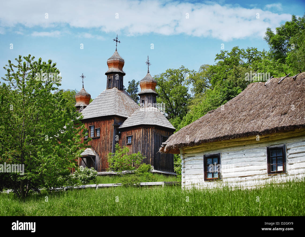 Traditional Slavonic village with wooden orthodox church and house with straw roof - Stock Image