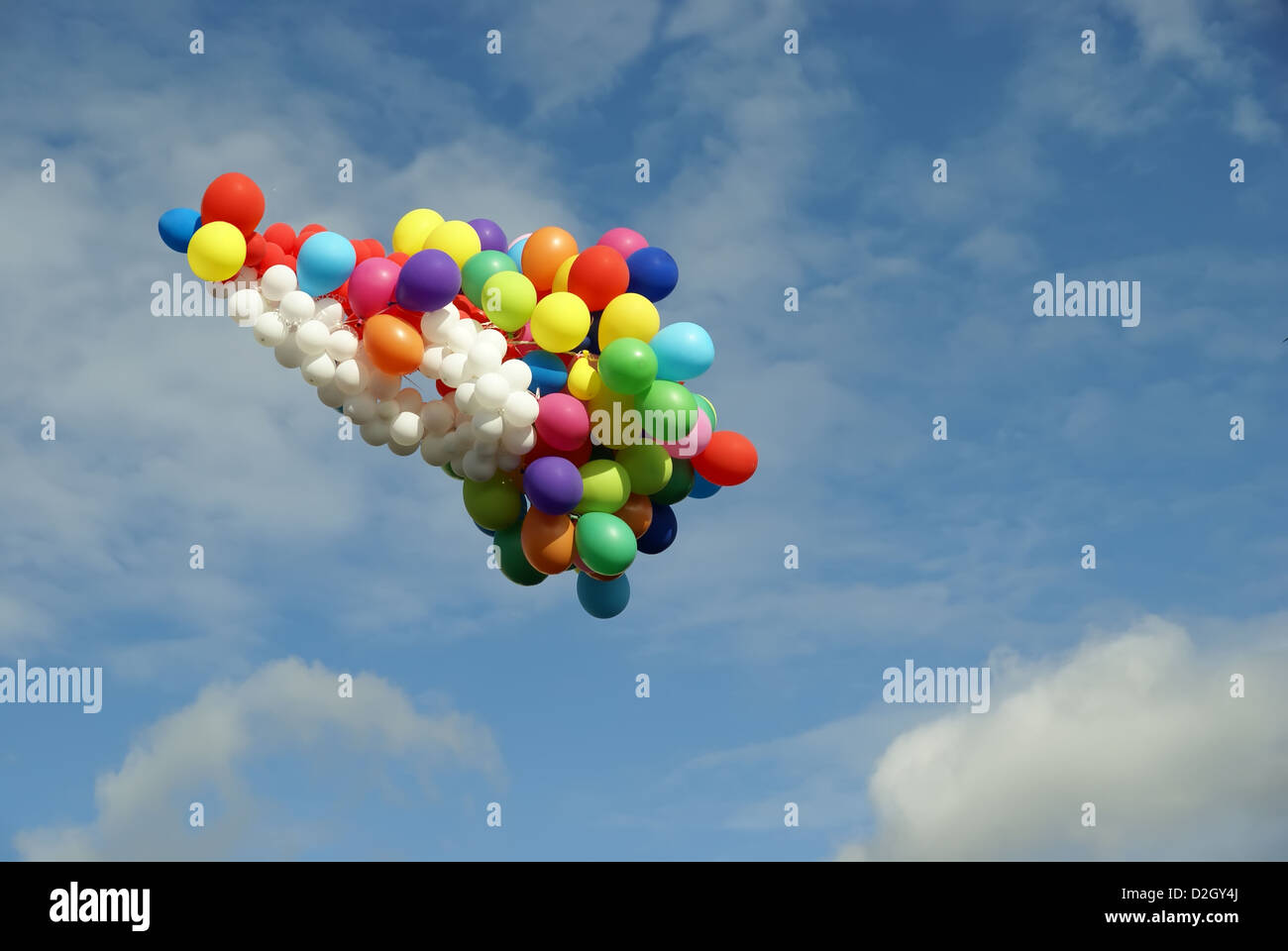 flying varicoloured balloons on a background blue sky - Stock Image