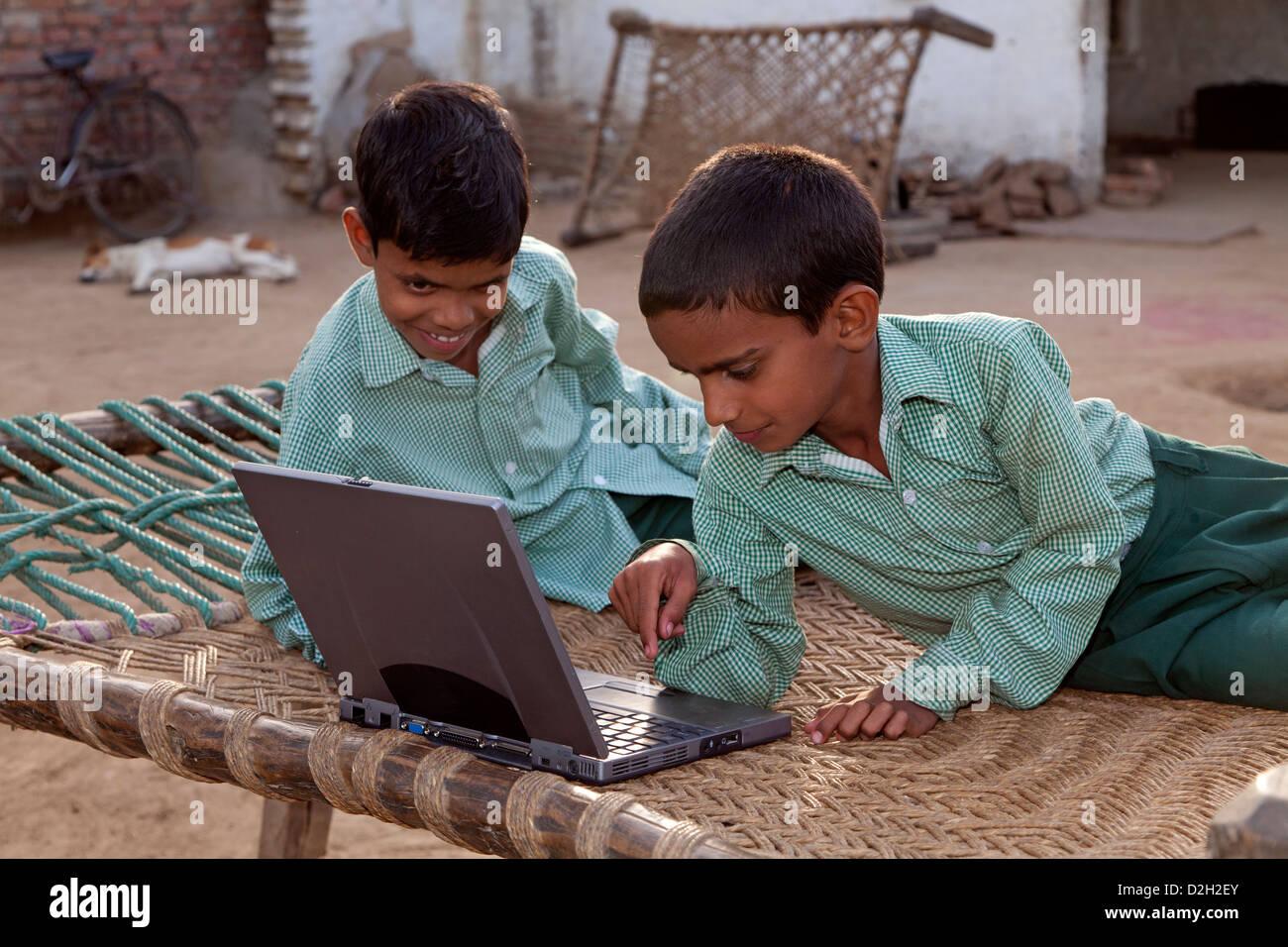India, Uttar Pradesh, Agra, young children in school uniform looking at laptop - Stock Image