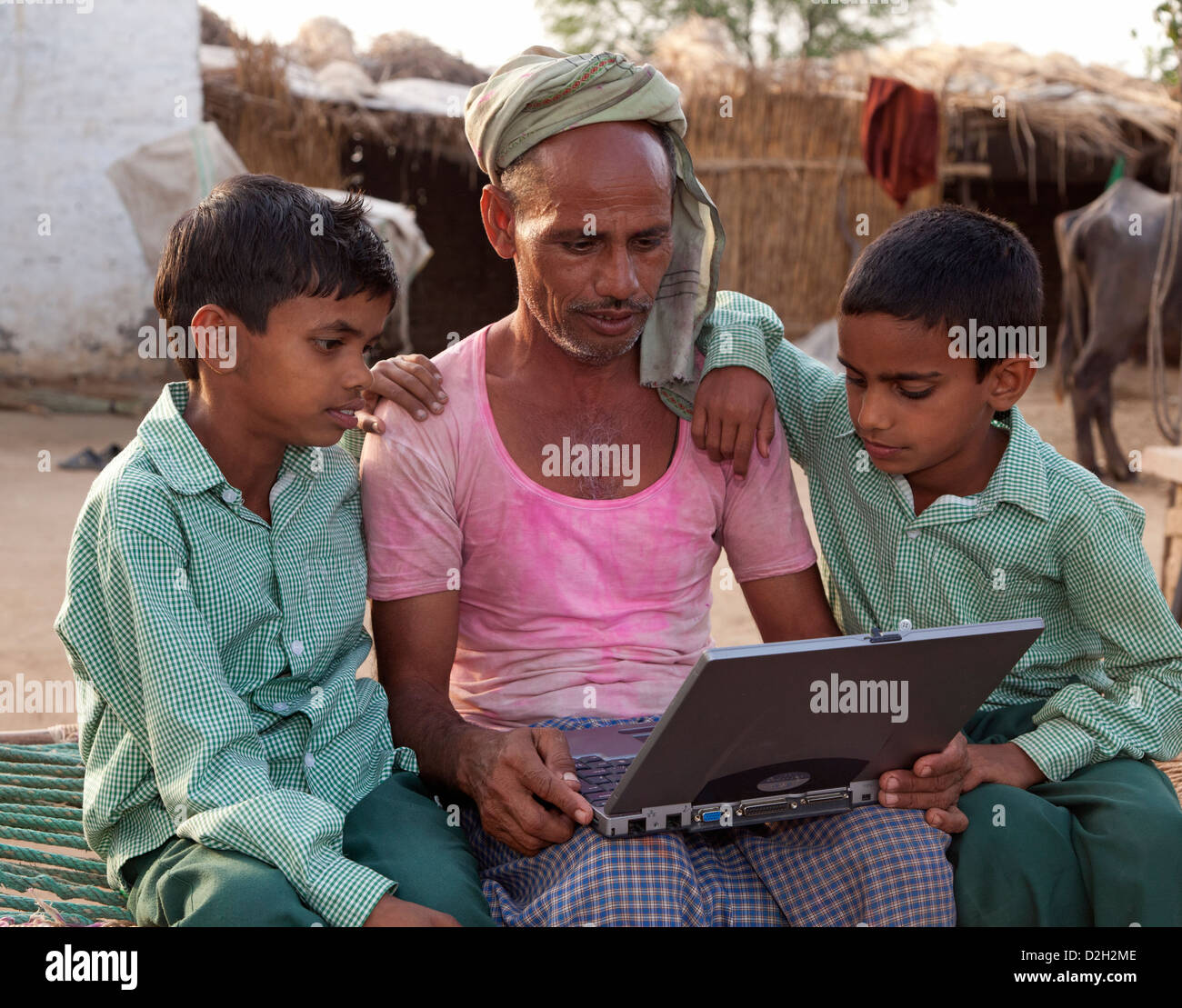 India,Uttar Pradesh, Agra, Two young children in school uniform studying laptop with father. - Stock Image