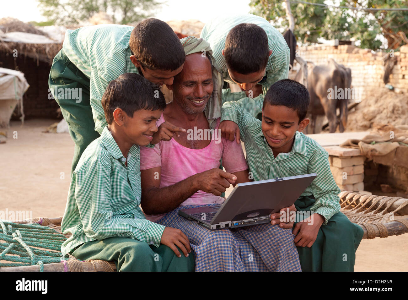India, Uttar Pradesh, Agra, Two young children in school uniform studying laptop with father. - Stock Image