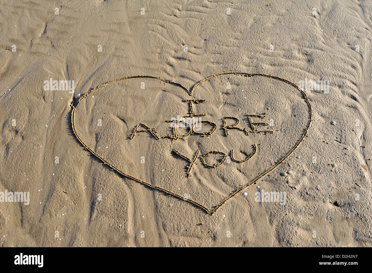 Word I Adore You written in sand - Stock Image
