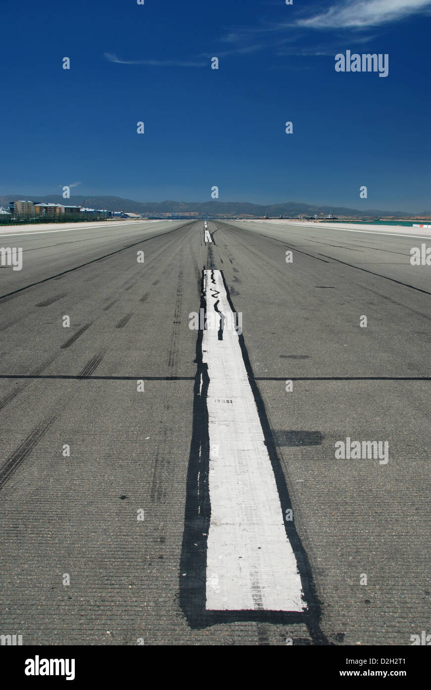 Large white stripe down the middle of a runway at an airport - Stock Image