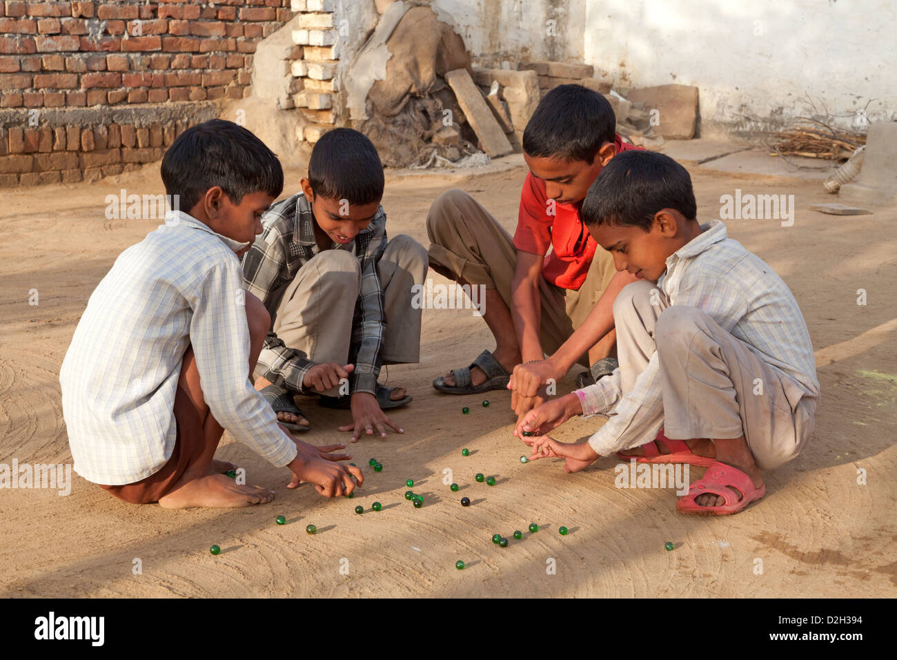 India, Uttar Pradesh, Agra, young children playing marbles outside village home - Stock Image