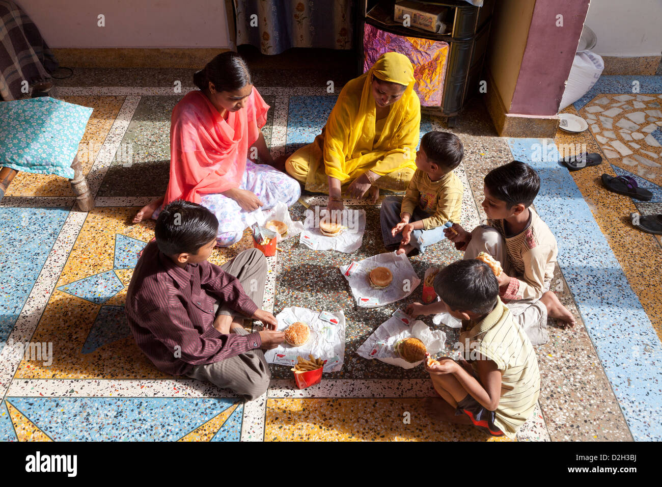 India, uttar Pradesh, Agra Mother and five children eating western style fast food - Stock Image