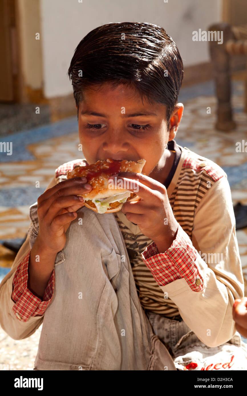 India, uttar Pradesh, Agra Indian boy eating western style fast food - Stock Image