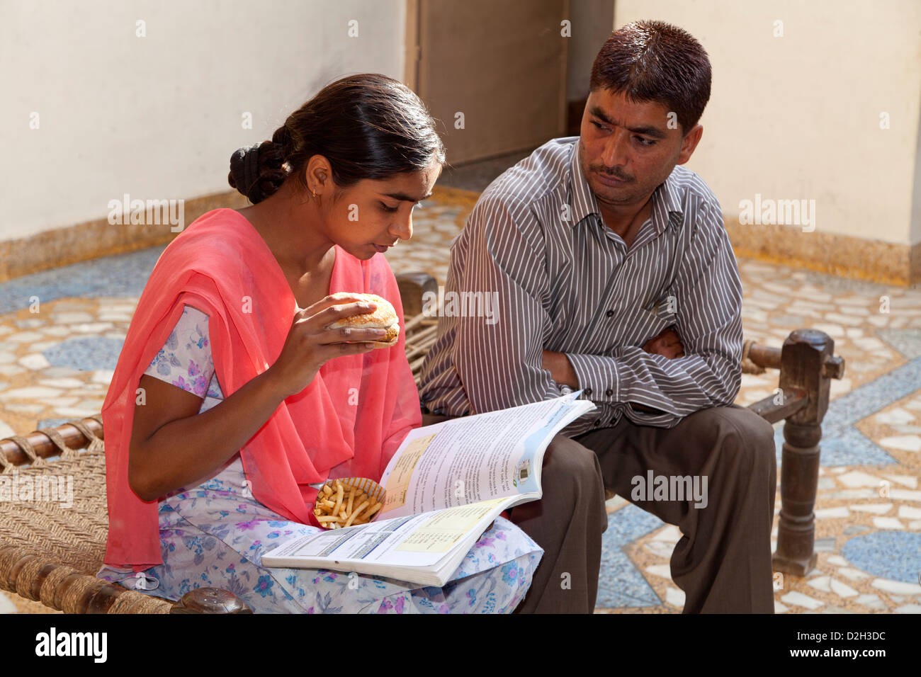 India, uttar Pradesh, Agra Indian girl eating western style fast food whilst studying and being watched disapprovingly - Stock Image