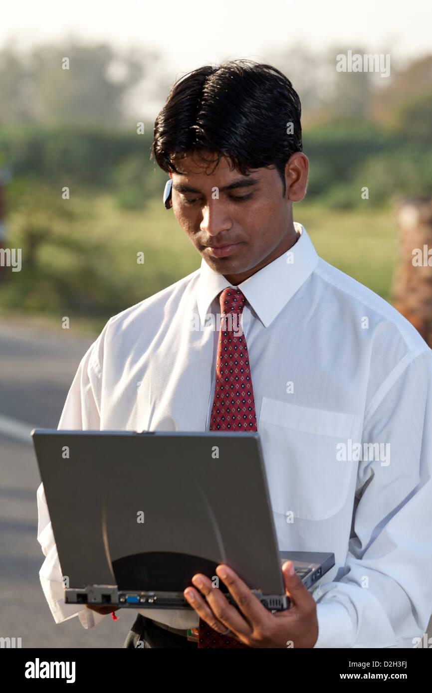 India, uttar Pradesh, Agra Indian businessman using laptop and wearing bluetooth headset - Stock Image