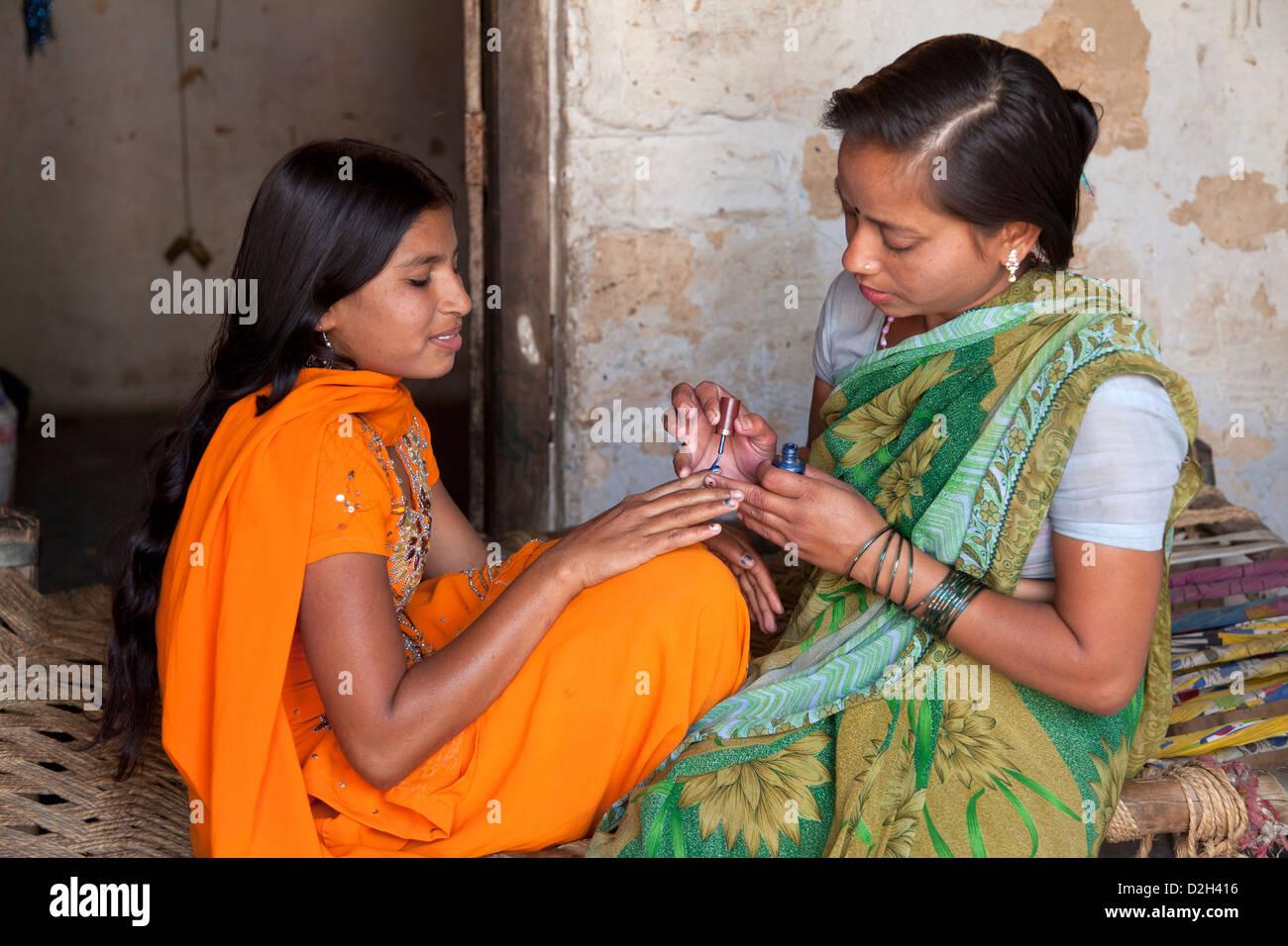 India, uttar Pradesh, Agra Older adult sister painting nails of younger teenage sister - Stock Image