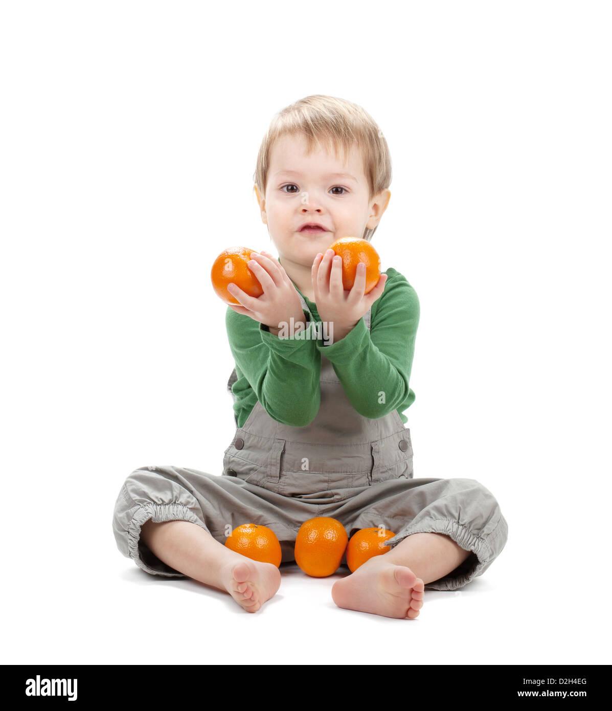 Baby with oranges. Isolated on white background - Stock Image