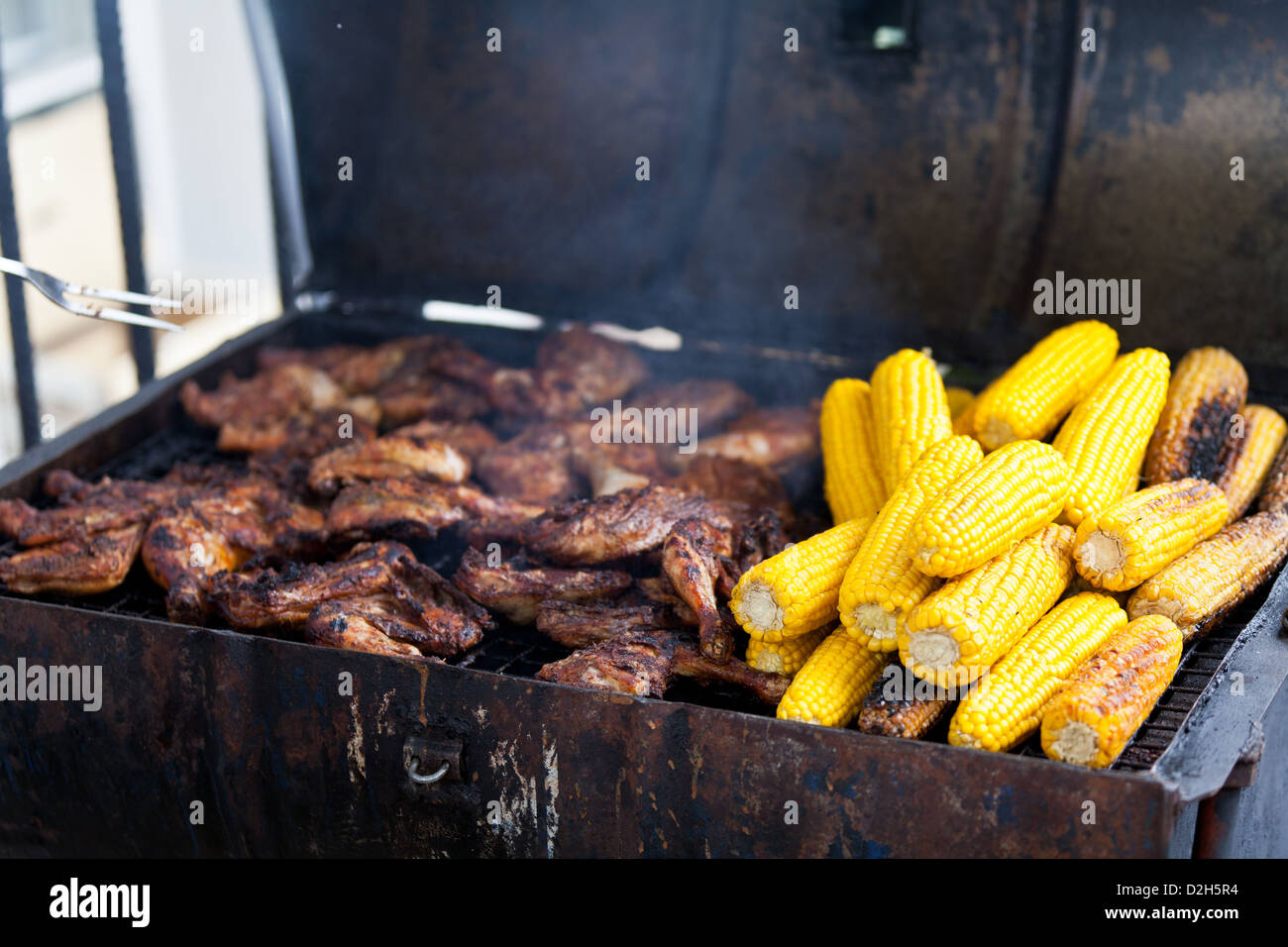 Jerk chicken and sweet corn being sold at an improvised street stall at the 2011 Notting Hill carnival. - Stock Image
