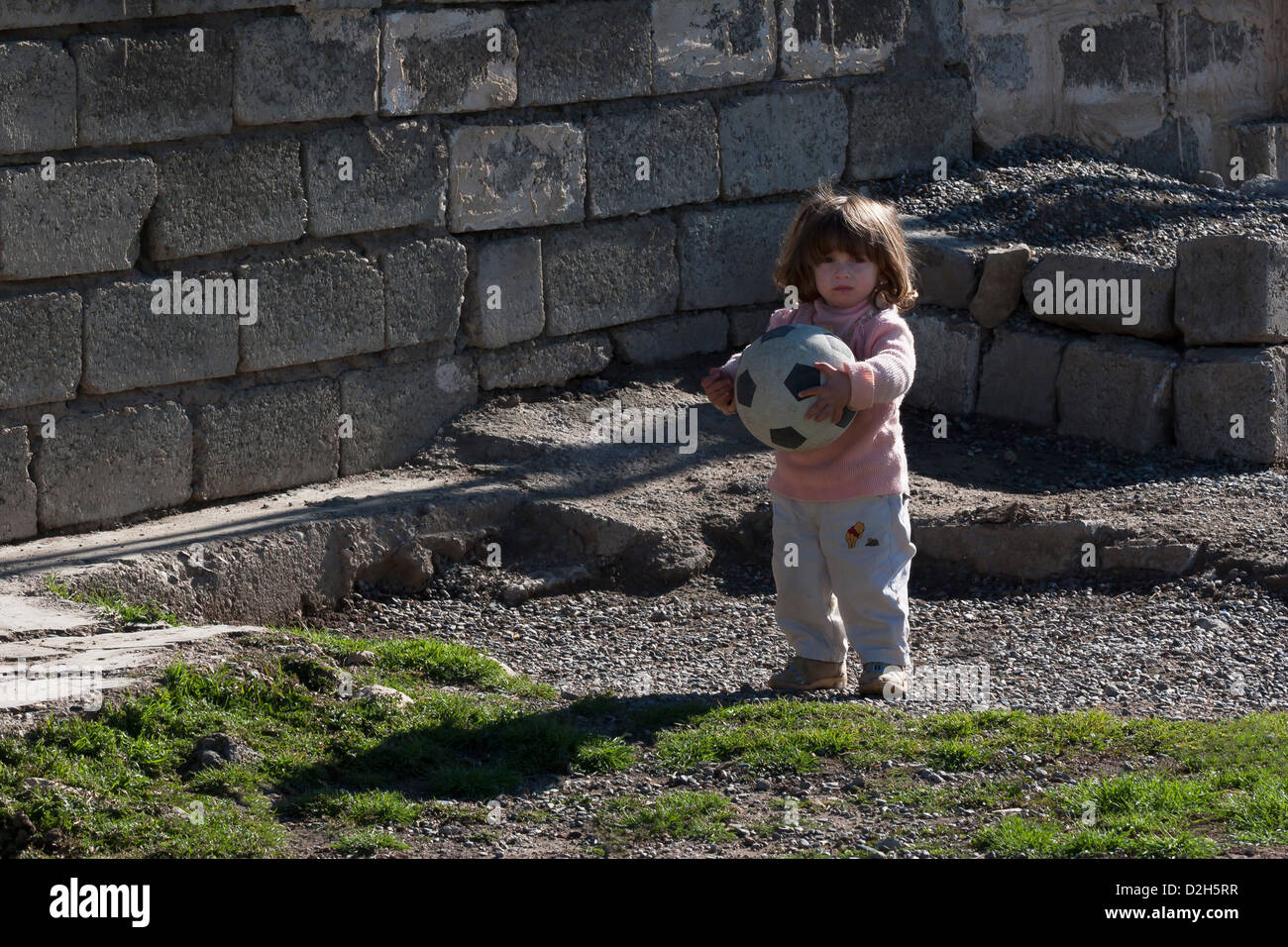 Kurdish refugee girl toddler, outside home in region of Iraqi Kurdistan, Northern Iraq - Stock Image