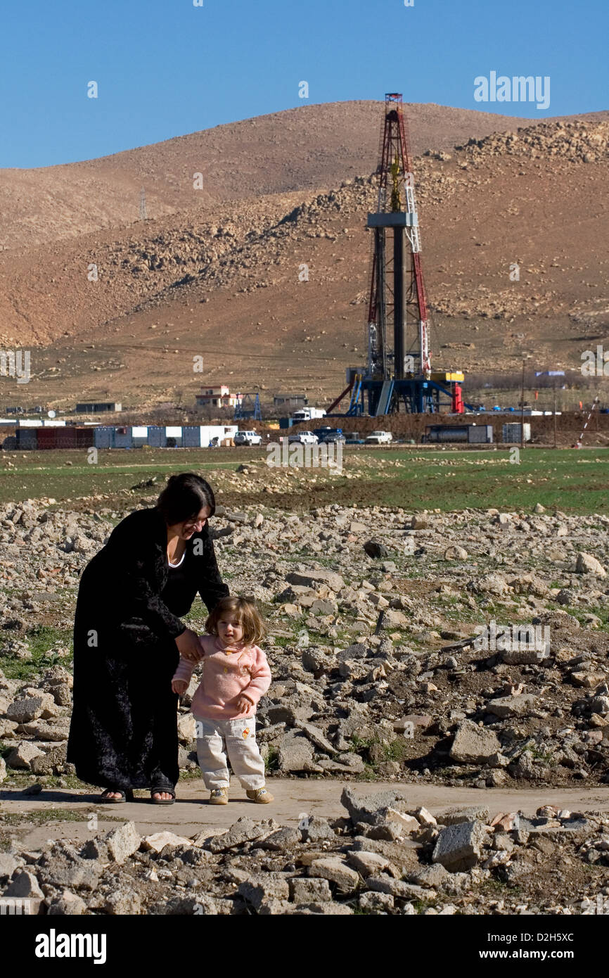 Kurdish refugee mother and girl toddler, near oil gas exploration rig, in mountainous region of Iraqi Kurdistan, - Stock Image