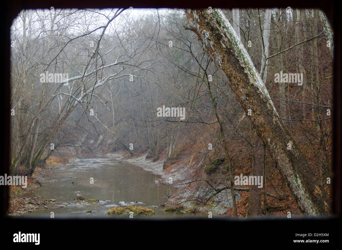 Looking out the window of the Rolling Stone Covered Bridge, just outside of Bainbridge, Indiana, at a winter scene. - Stock Image