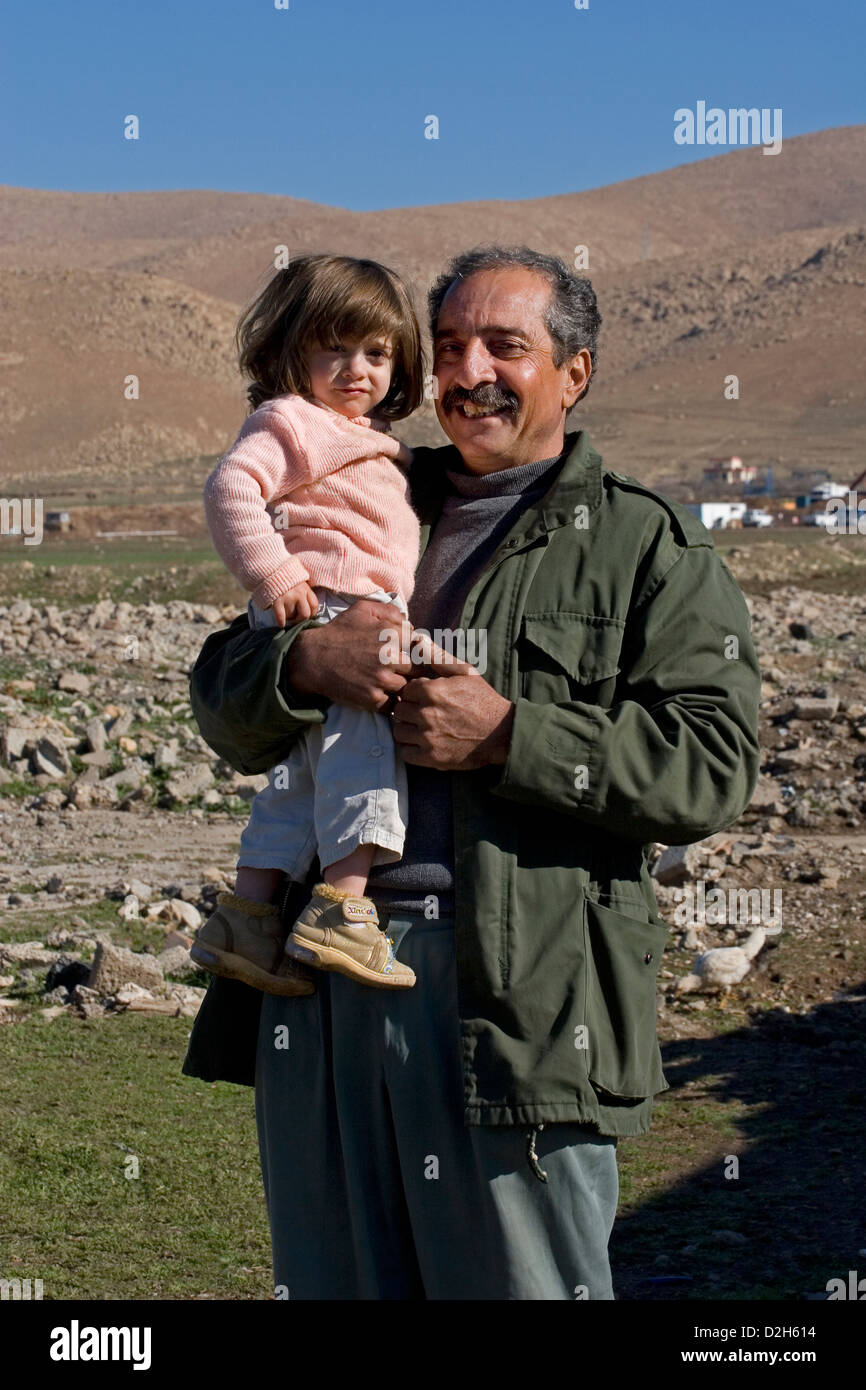 Kurdish refugee grandfather holding 3 year old granddaughter outside in moutainous region of Kurdistan, Northern - Stock Image