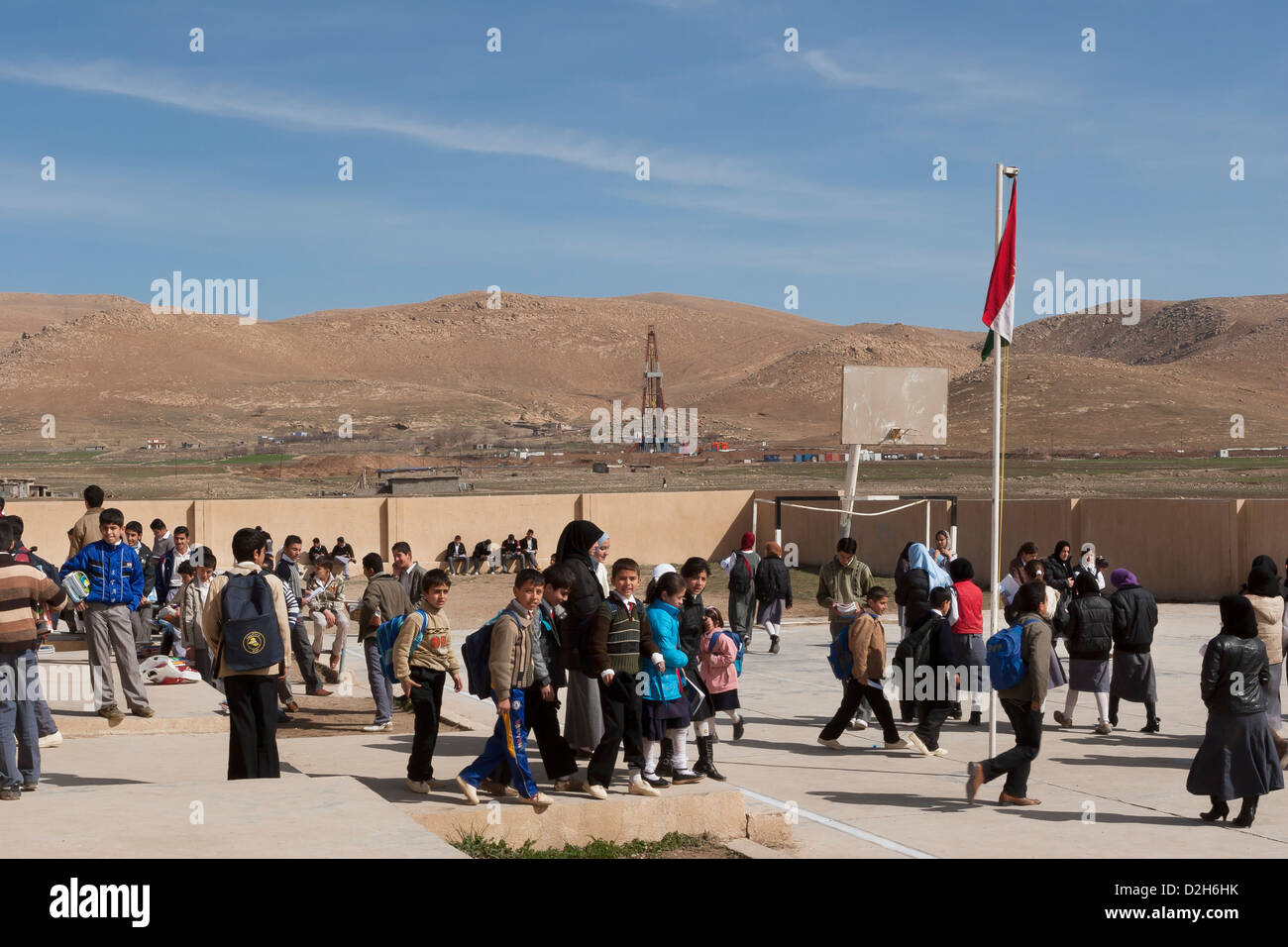 Primary and senior students in playground outside Iraqi Kurdish school in Northern Iraq  with oil exploration rig - Stock Image