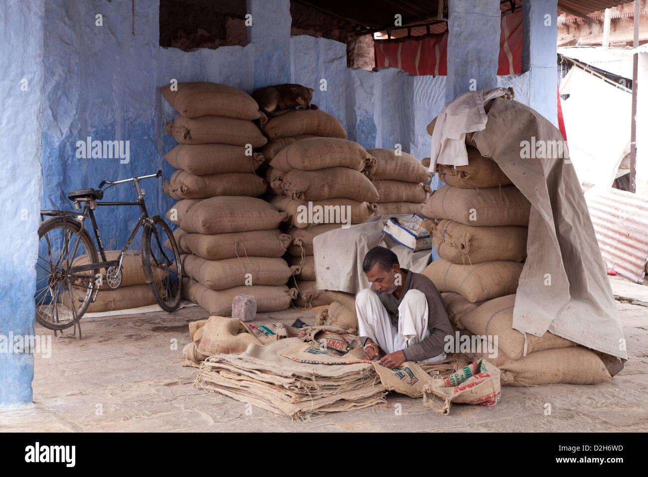 India, Rajasthan, Jodhpur man repairing hessian sacking used for carrying grain - Stock Image
