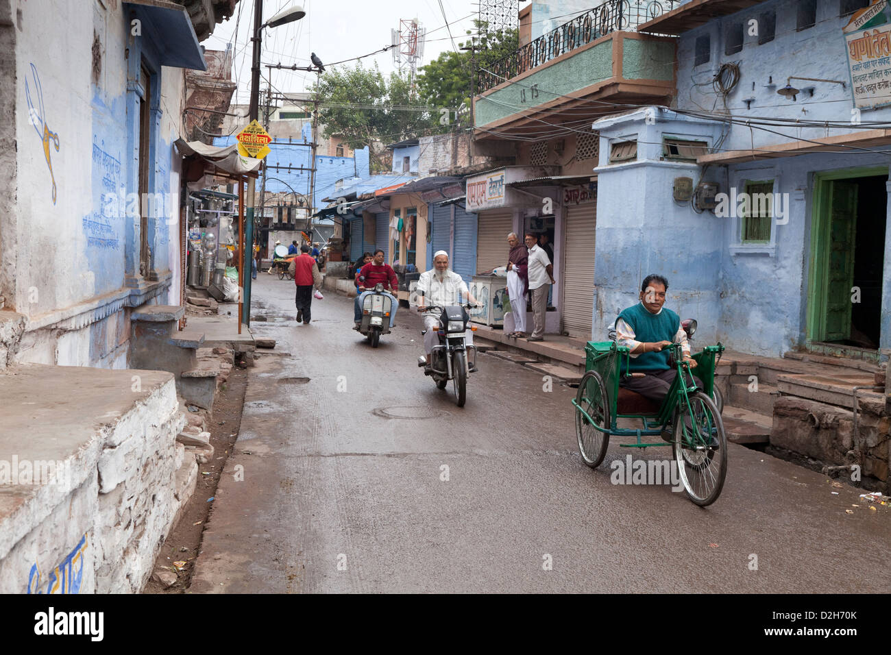 India, Rajasthan, Jodhpur street scene showing man using commonly used tricycle for people with polio in India - Stock Image