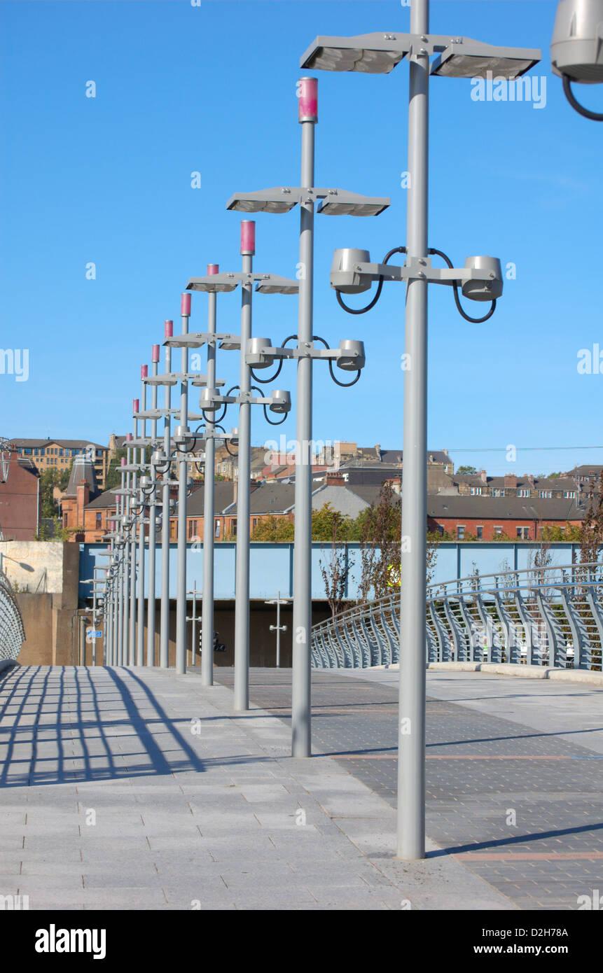 Row of lamp posts on a footbridge in Glasgow, Scotland - Stock Image