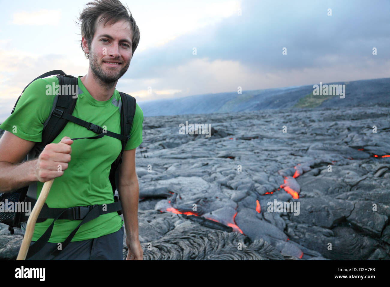 Hawaii hiker hiking by flowing lava from Kilauea volcano around Hawaii volcanoes national park, USA. Young caucasian - Stock Image
